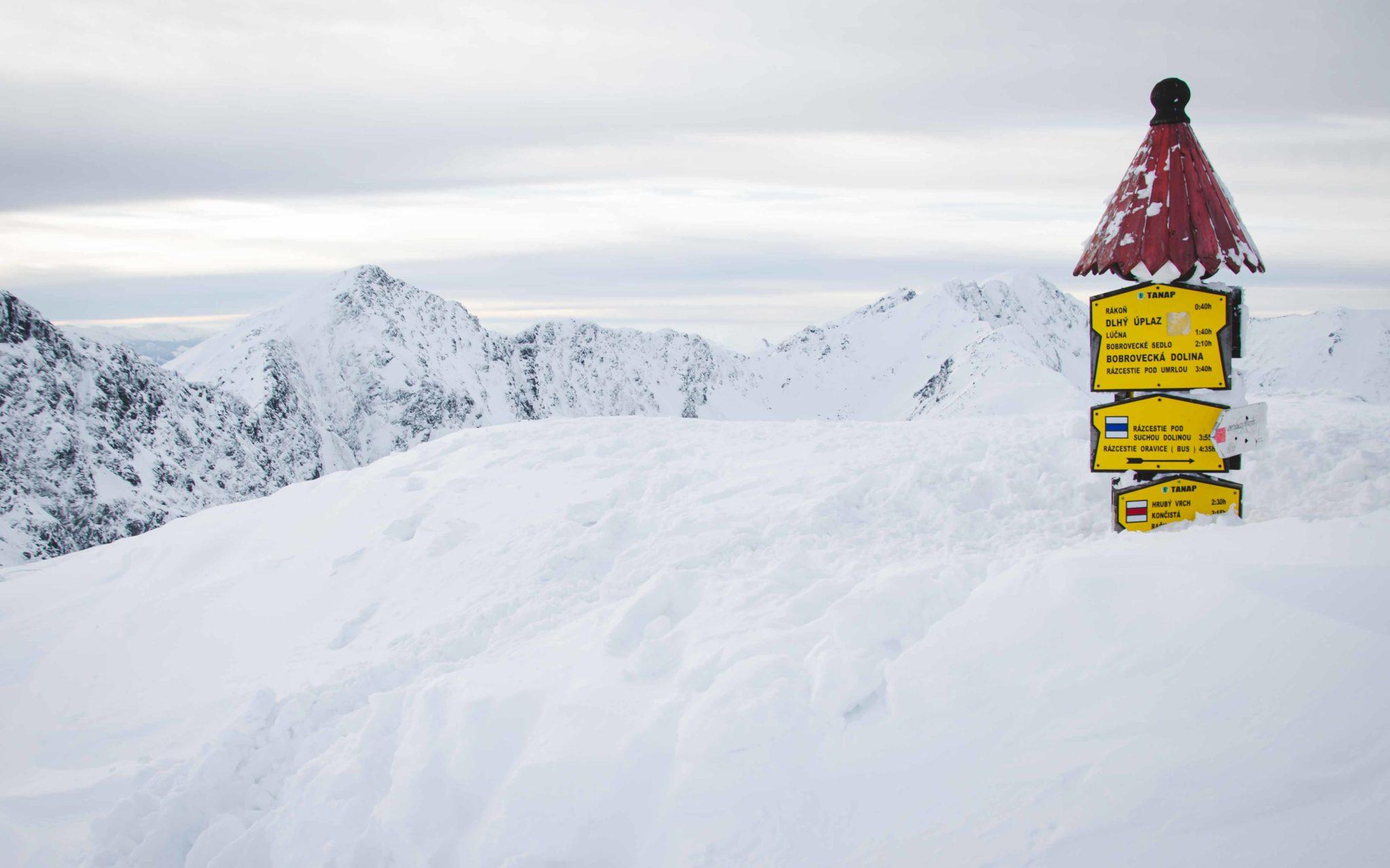 Słup z tabliczkami zakopany w śniegu na szczycie