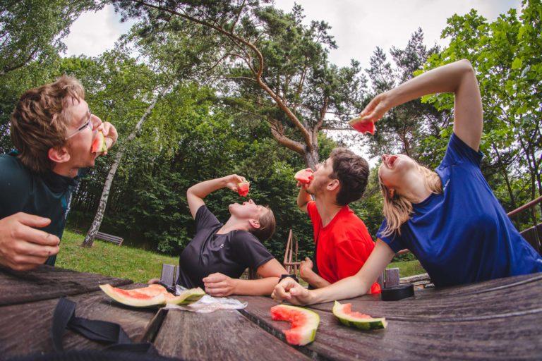 Cztery osoby jedzą kawałki arbuza