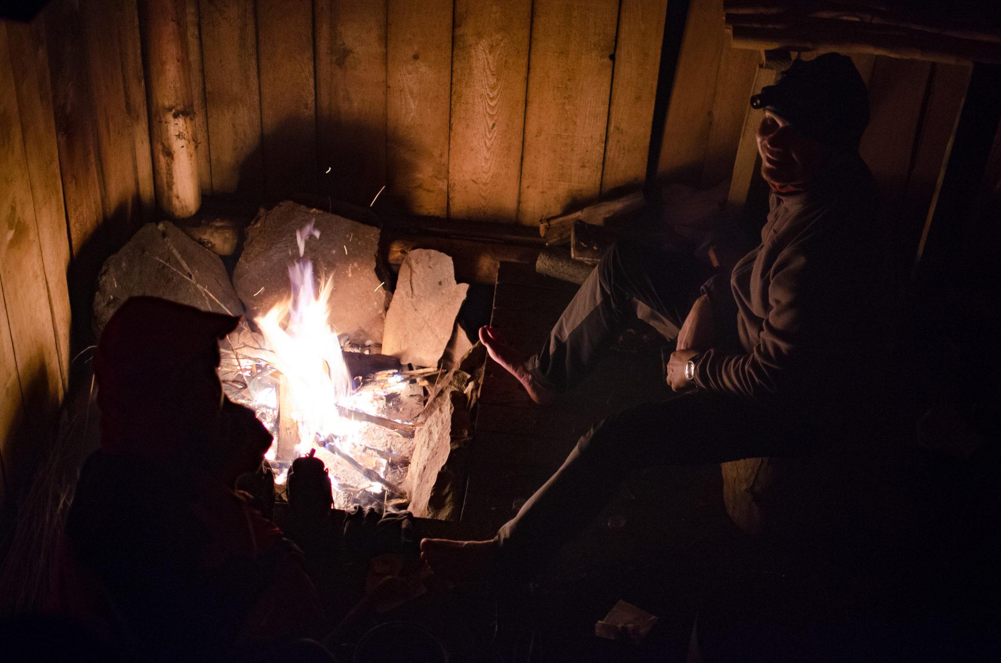 Mężczyzna siedzie przy ognisku