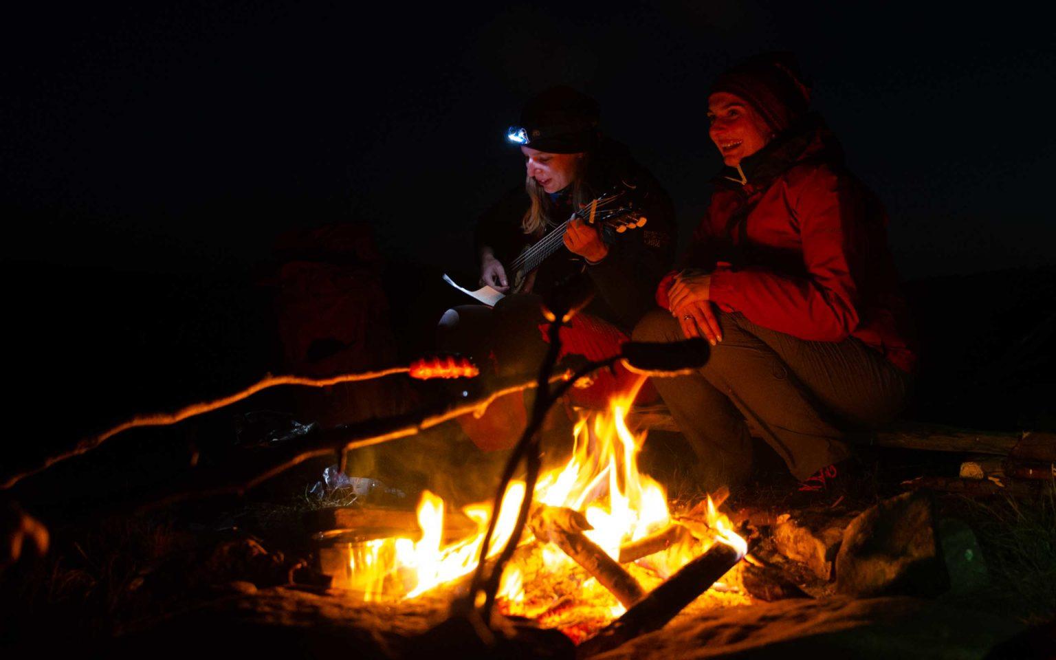 Dwie kobiety z gitarą siedzą przy ognisku w nocy
