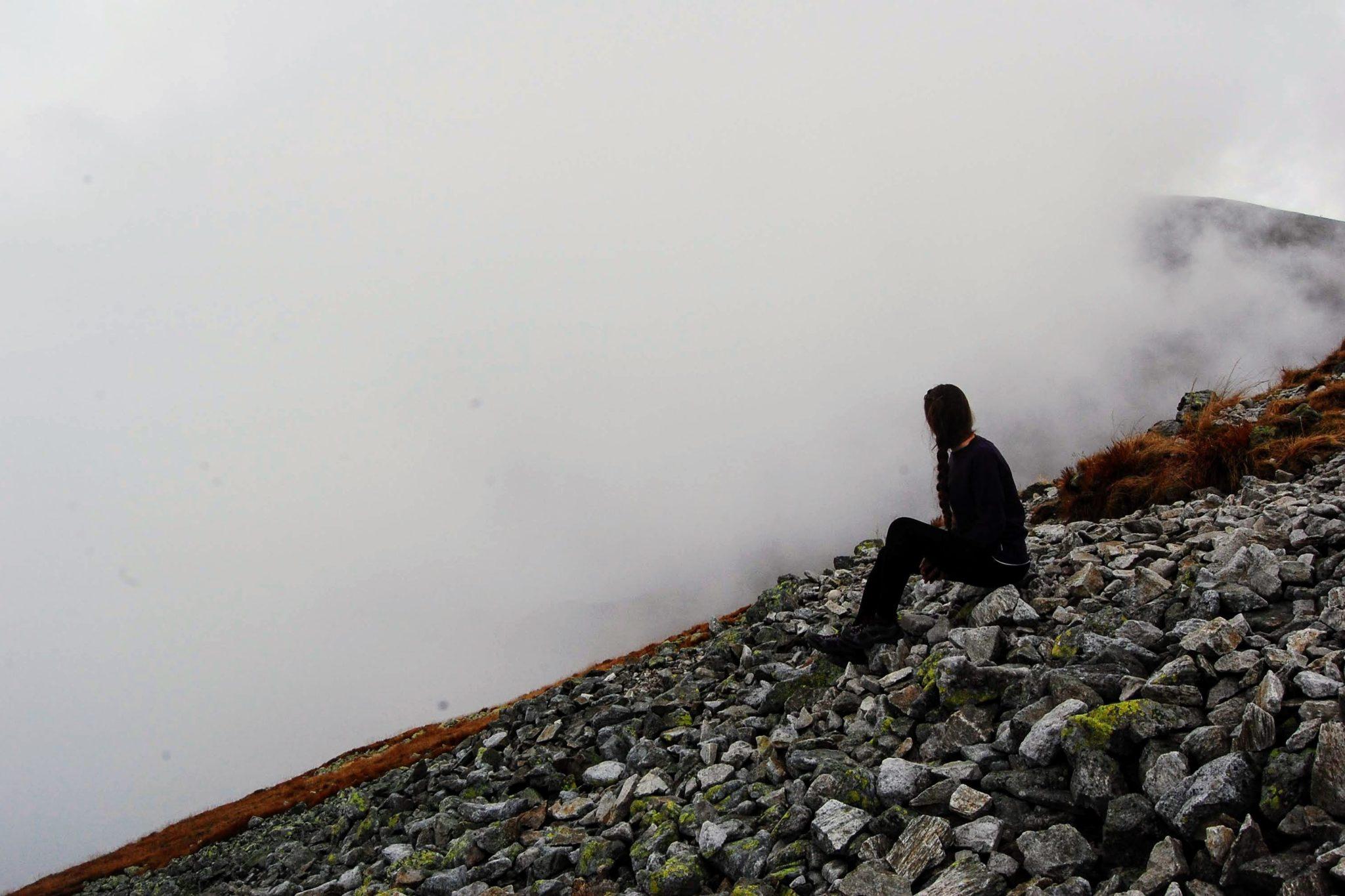 Kobieta siedzi w mgle na Kopie Kondrackiej