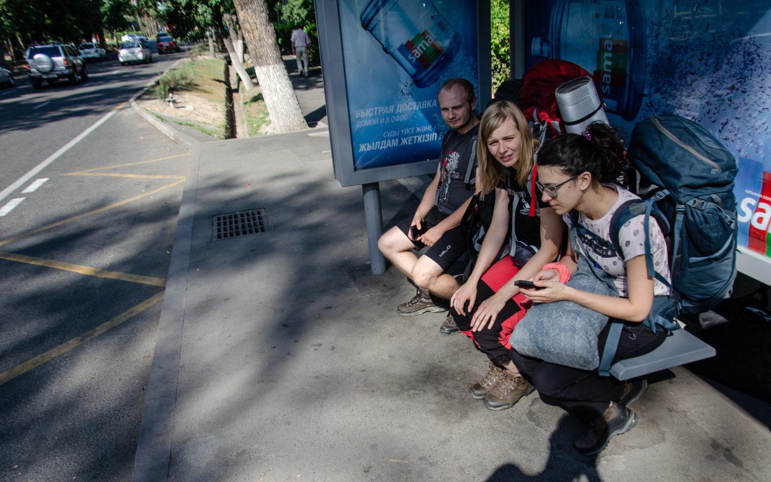 Trzy osoby siedzą z plecakami na przystanku autobusowym