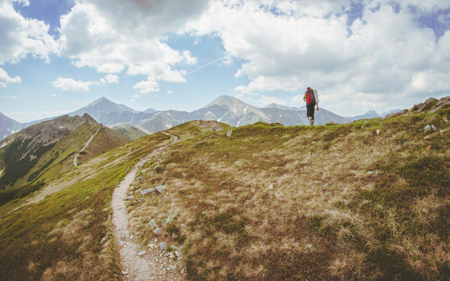 Mężczyzna idzie na grani w Tatrach. W tle Tatry Zachodnie