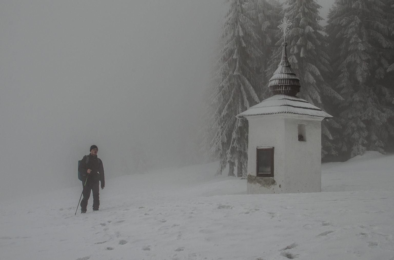 Mężczyzna idzie po mglistym szlaku obok kapliczki w górach