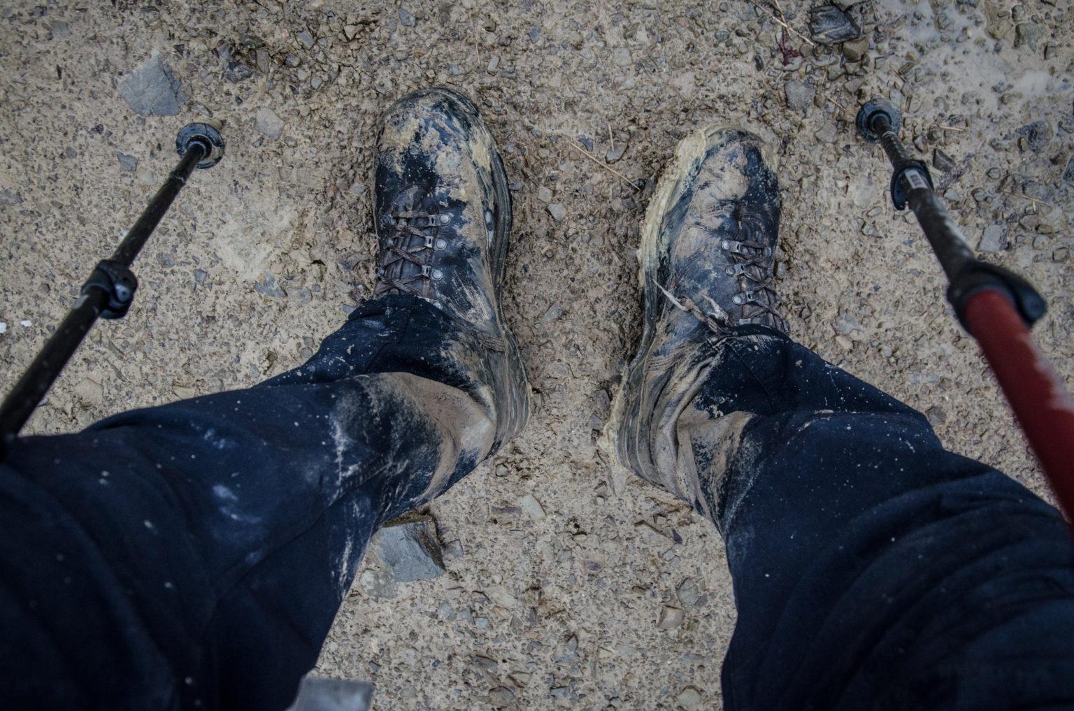 Zabłocone buty i kije trekkingowe