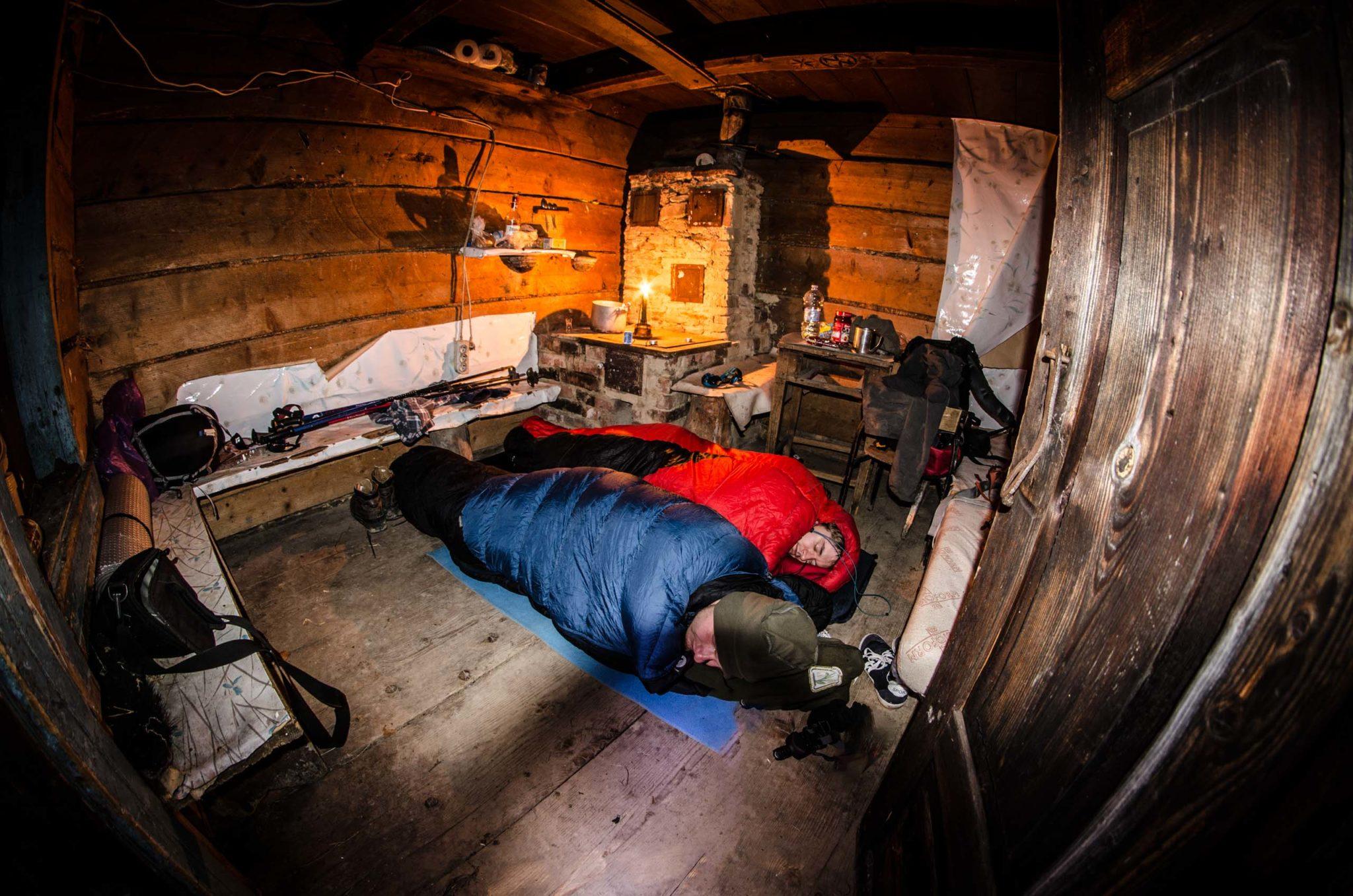 Dwóch mężczyzn w śpiworach leży na podłodze w bacówce w górach