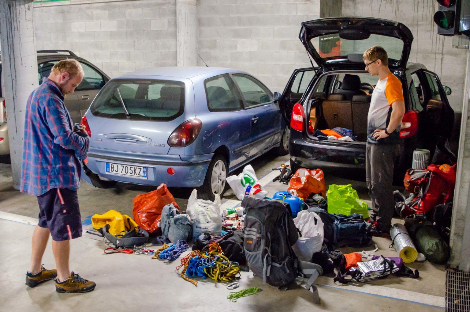 Dwóch mężczyzn stoi przy rzeczach wyciągniętych z auta na parkingu
