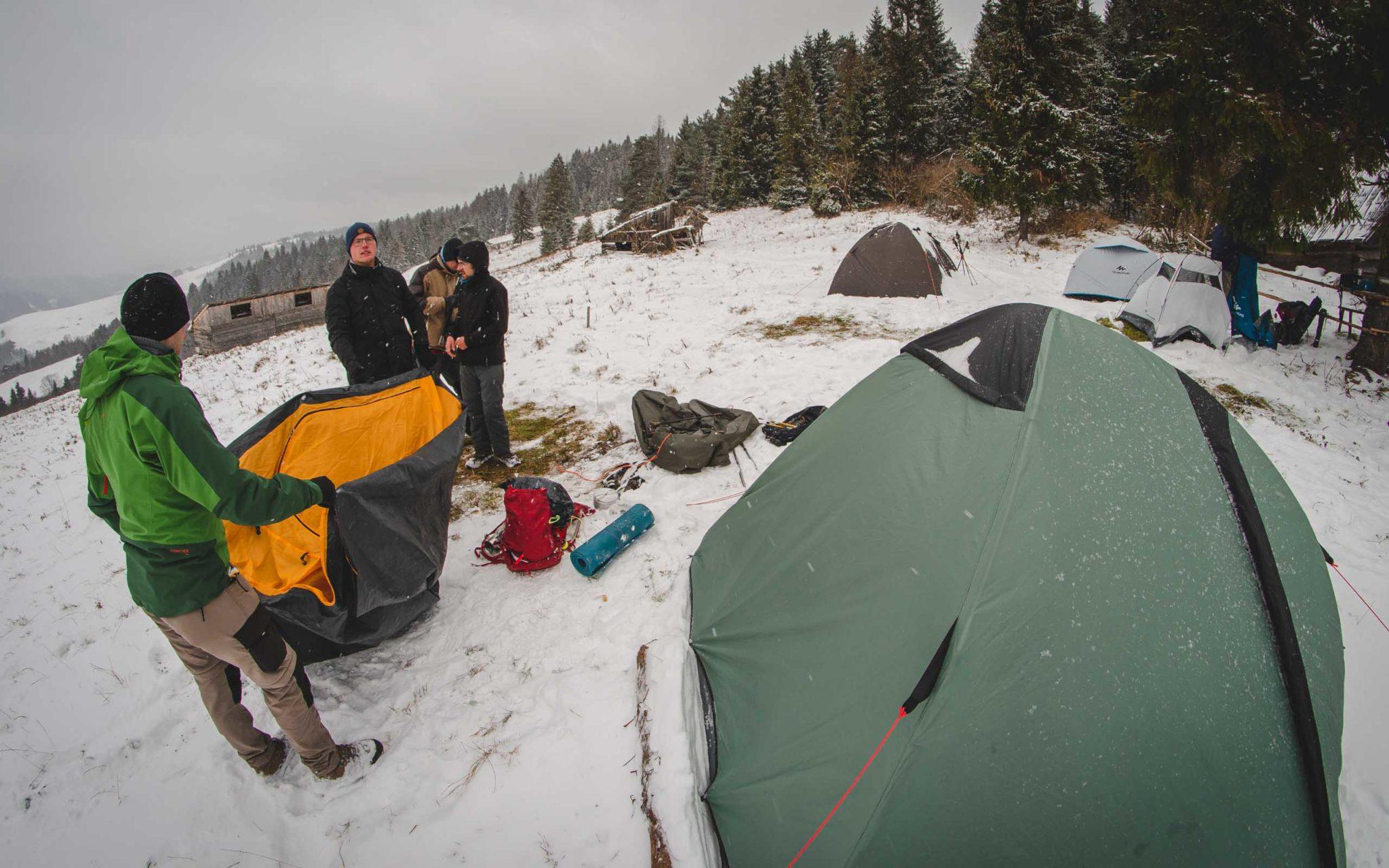 Grupa osób rozkłada namiot na śniegu
