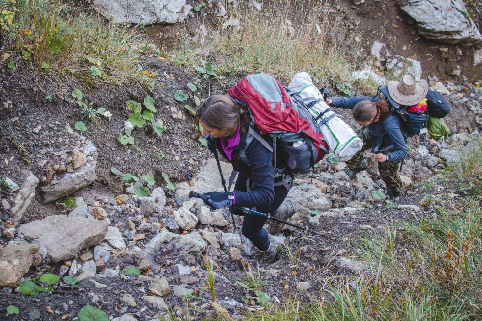 Dwie kobiety podchodzą stromym podejściem w górach.