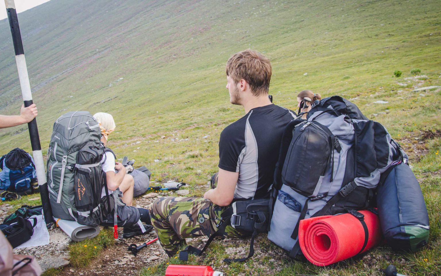Mężczyzna siedzi z ciężkim plecakiem na plecach