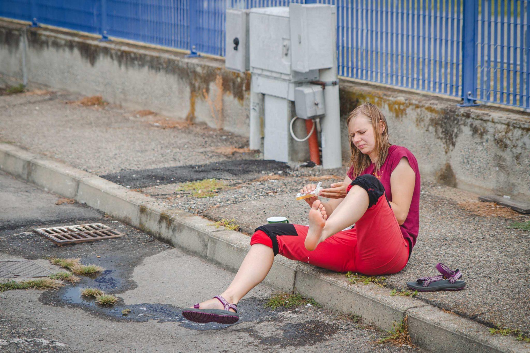 Kobieta siedzi na krawężniku i myje nogi