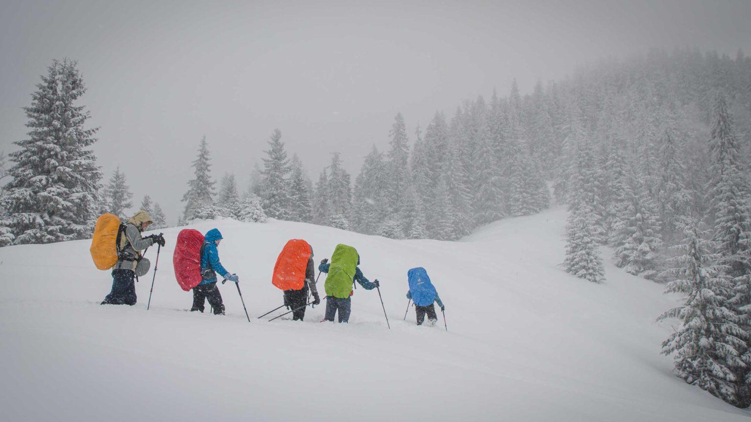 Grupa osób idzie w głębokim śniegu w górach
