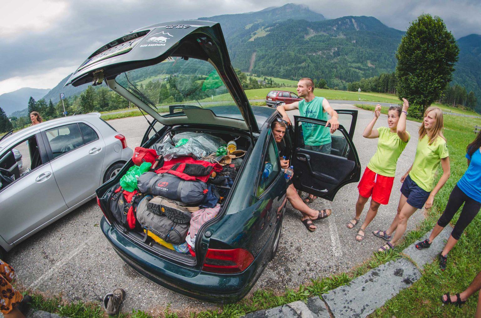 Grupa osób stoi przy wypakowanym rzeczami samochodzie