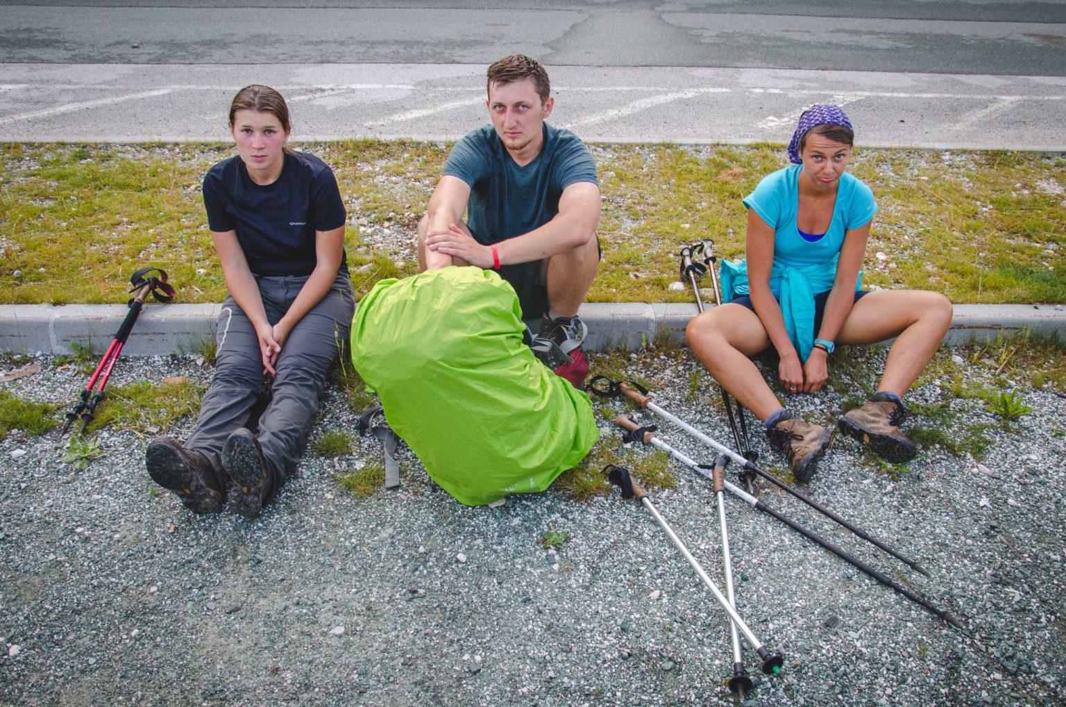 Trzy osoby zmęczone siedzą na krawężniku
