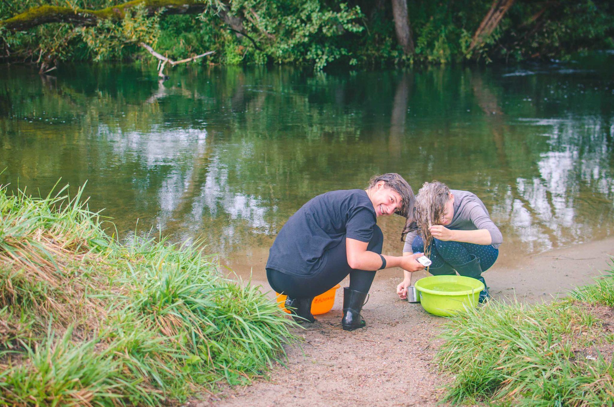 Dwie kobiety myją włosy nad rzeką