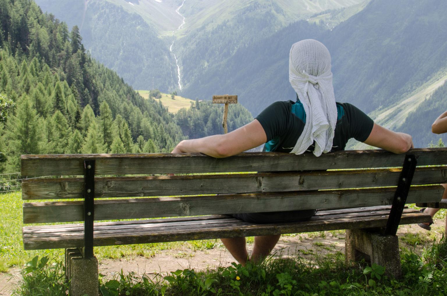 Mężczyzna siedzi na ławce w górach