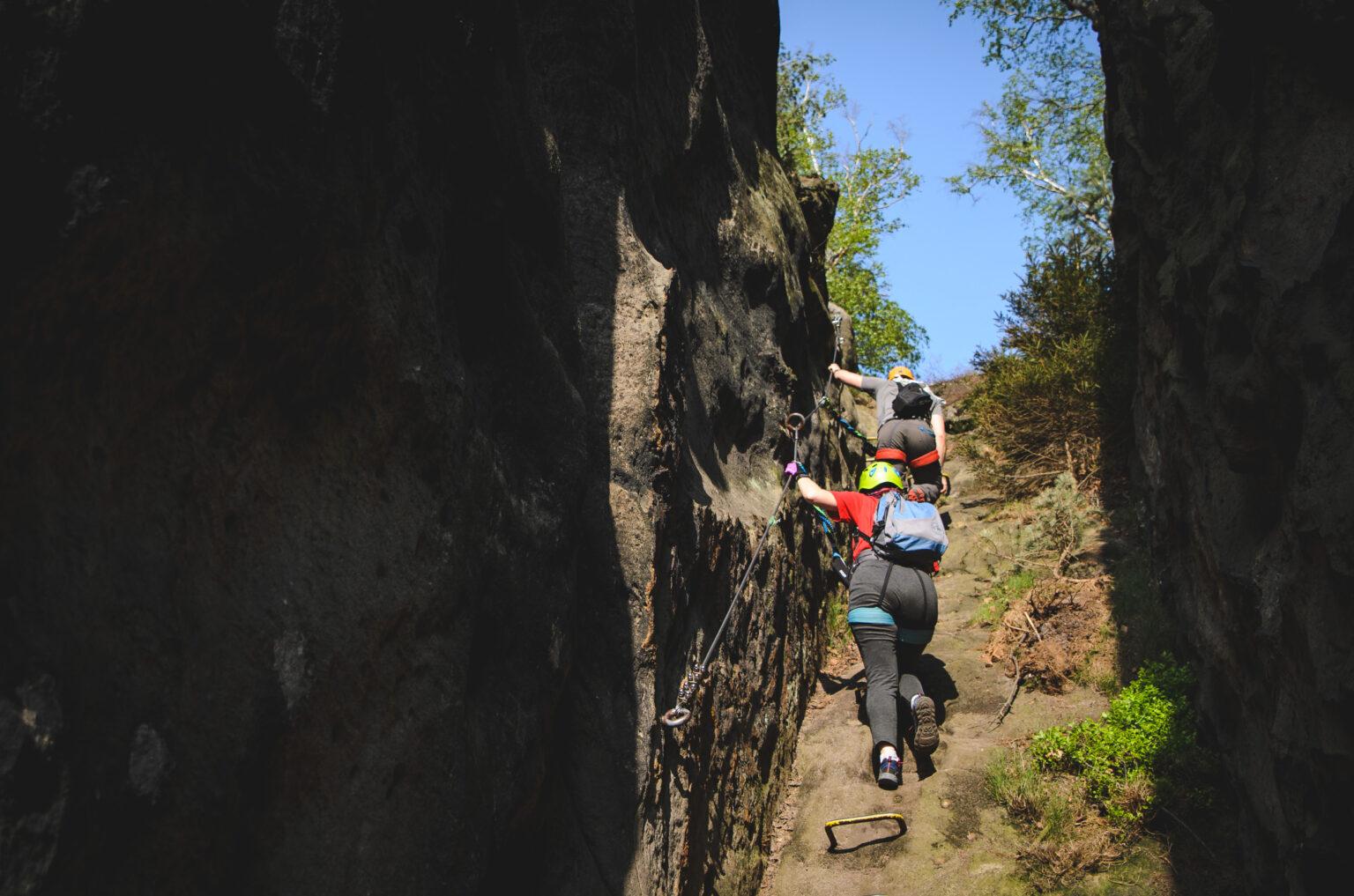 Turyści wchodzą po klamrach na ferracie