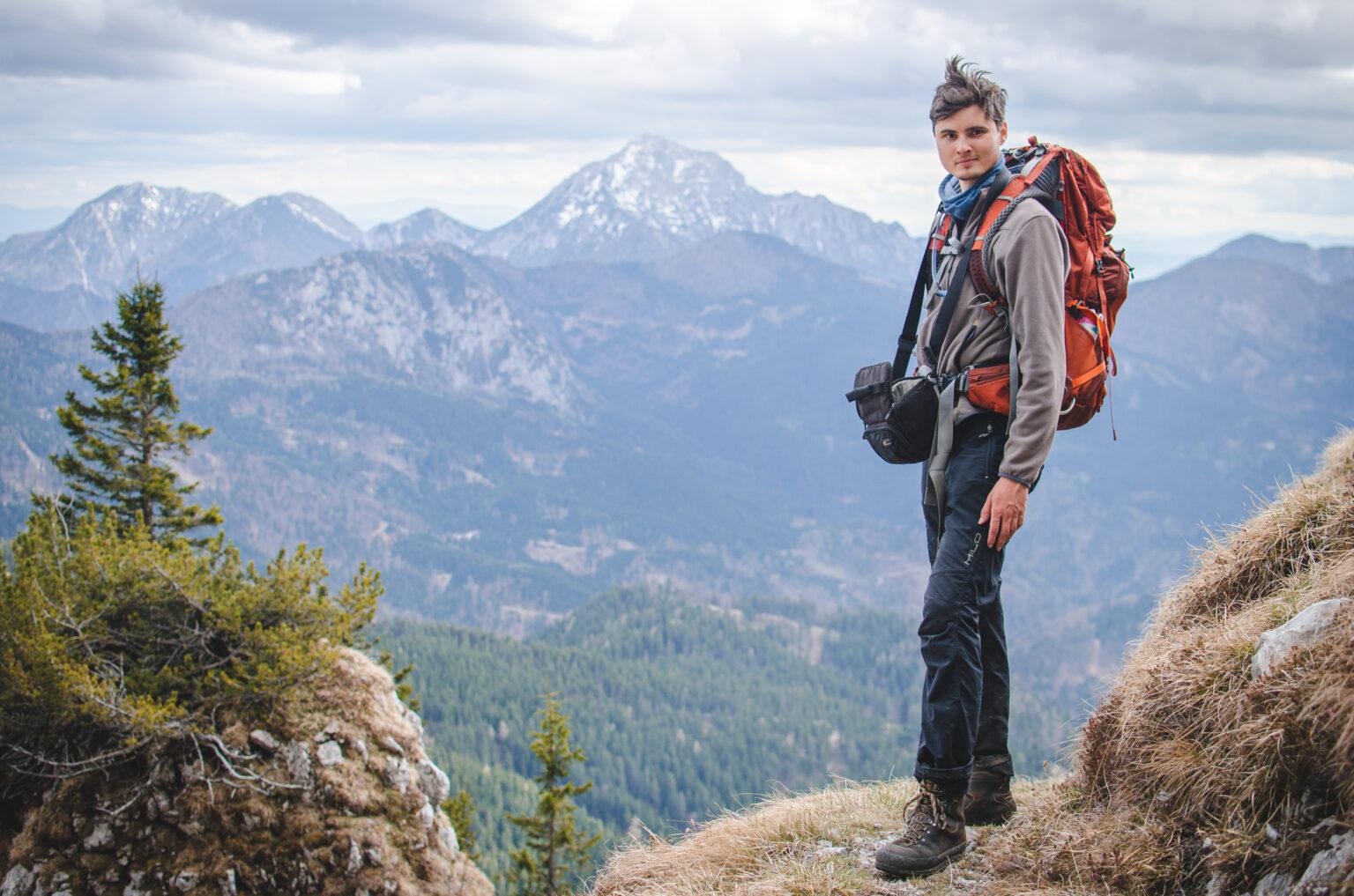 Turysta z plecakiem i aparatem, w tle góry - Storžič, Alpy Kamnicko-Sawińskie