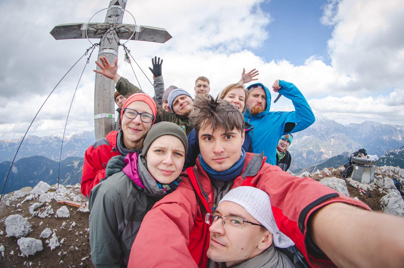 Grupa osób stojąca przy krzyżu na szczycie Storzica
