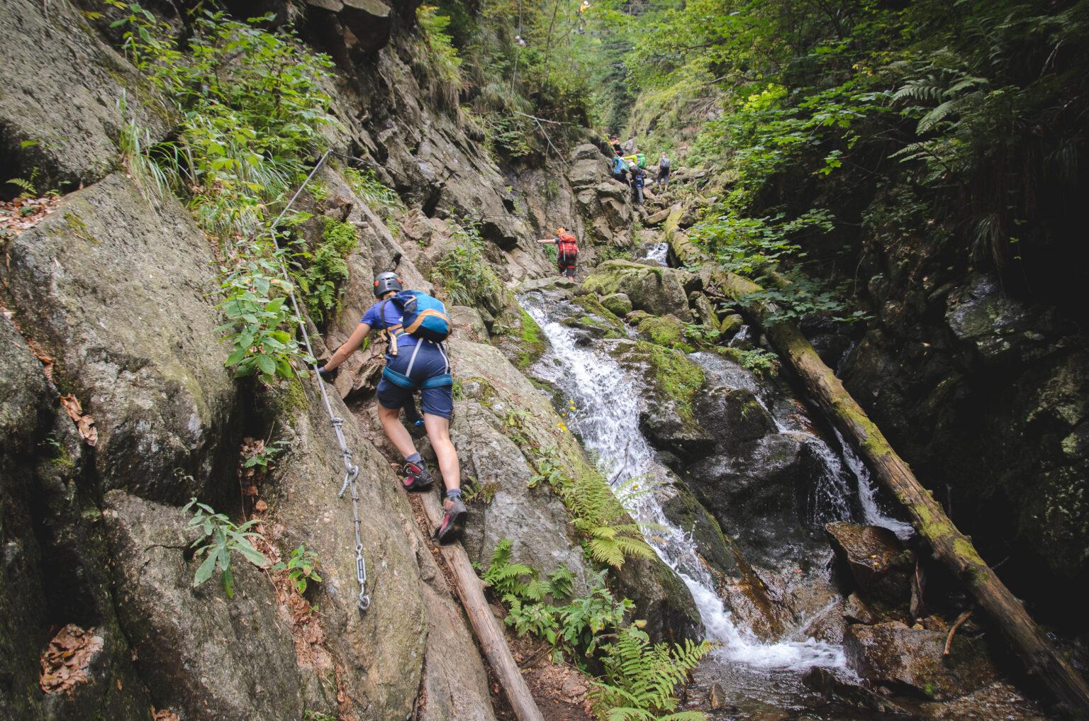 Turyści przechodzą ferratą nad rzeką