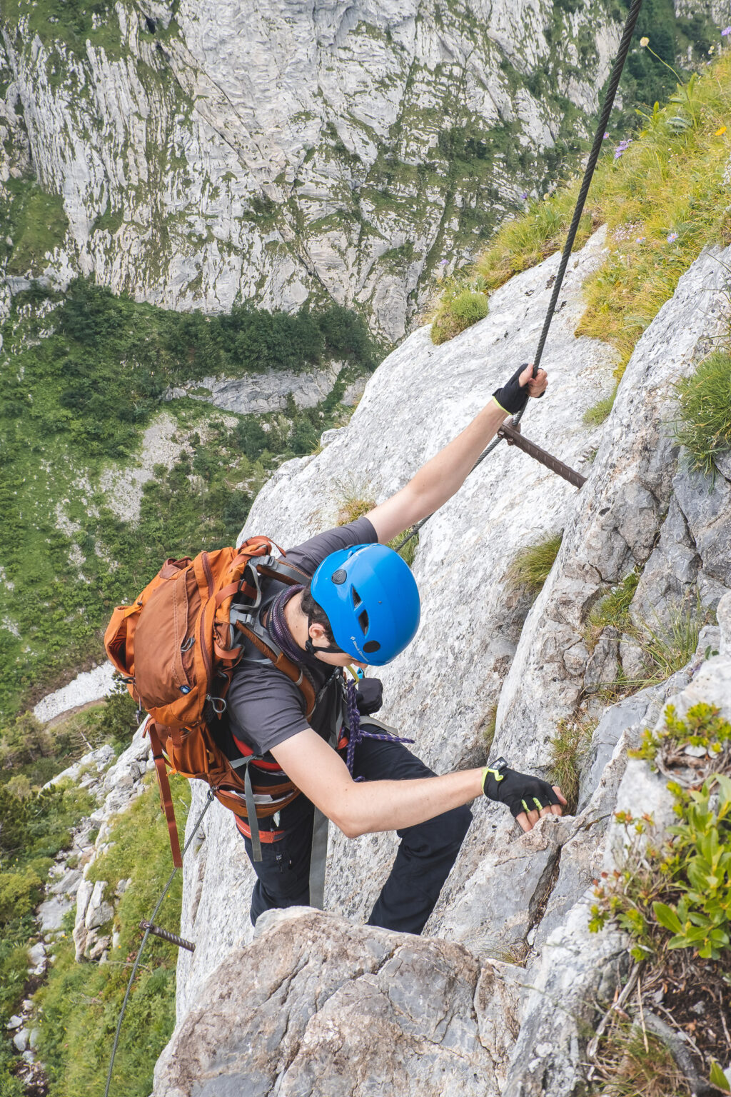 Błażej z plecakiem w niebieskim kasku wspina się po ferracie na Plockenpass