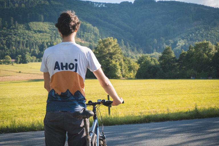 """Błażej w koszulce z napisem """"Ahoj"""" trzymający rower"""